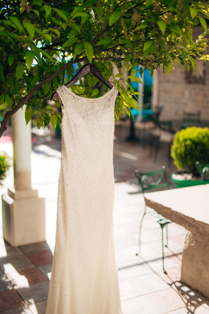 The brides dress on a hanger in the green in Montenegro