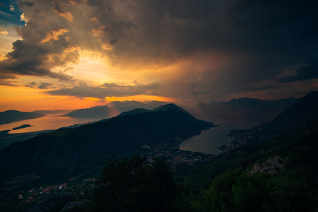 Sunset in Montenegro over the mountains and the sea. Orange sunsets.