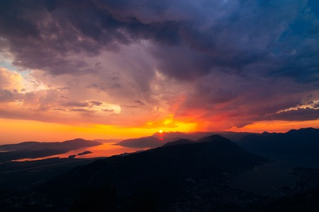 Sunset in Montenegro over the mountains and the sea. Orange sunsets. Фото со стока - 87578053