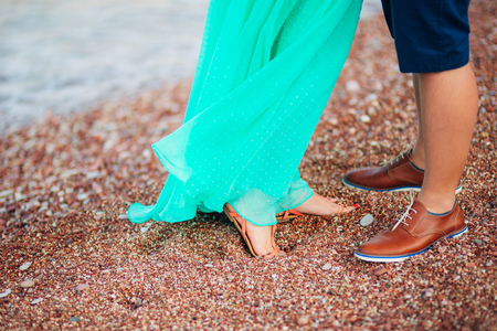 Womens and mens feet in the sand. Wedding in Montenegro