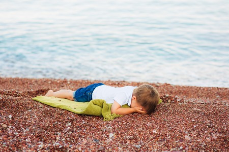 A frustrated child cries on a pebble beach in Montenegro.