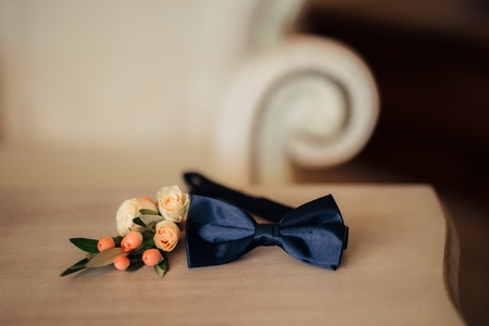 Bow tie and boutonniere on a wooden table