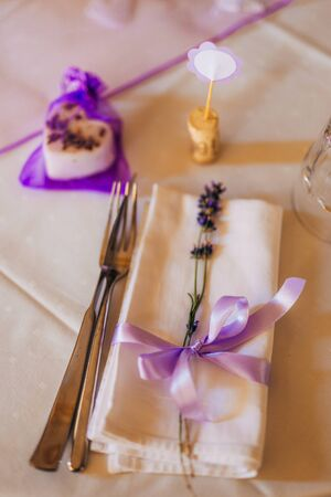 Wedding table setting at a banquet. A plate and instruments tied with a purple ribbon.