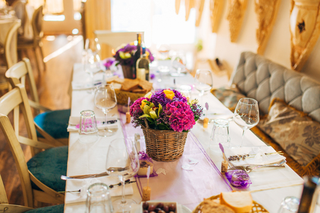 dining table and chairs: Flower compositions on the wedding table in rustic style. Wedding decorations with their own hands. Wedding in Montenegro. Stock Photo