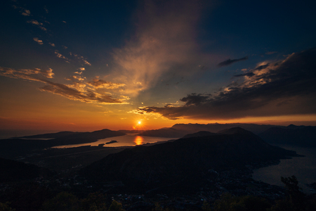 curve road: Sunset in Montenegro over the mountains and the sea. Orange sunsets.
