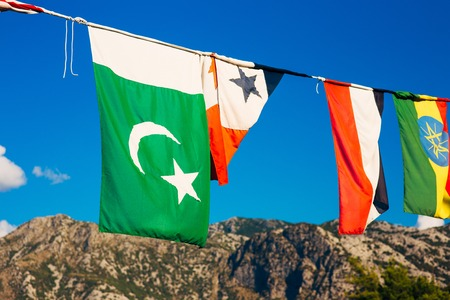 The flag of Pakistan is hanging on a rope with other flags against the background of the sky and mountains.