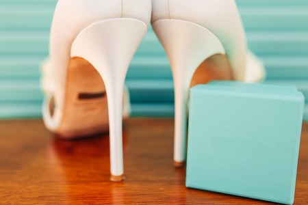 objects: Wedding shoes of the bride on a blue wooden background. Wedding in Montenegro. Stock Photo