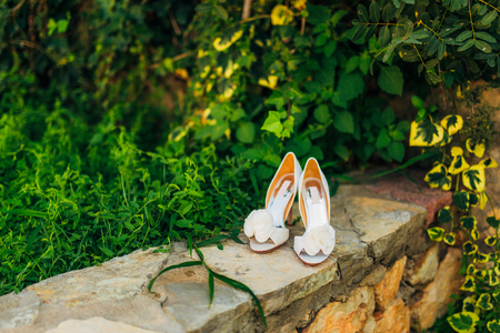 Wedding shoes on a stone border against a background of green leaves. Weddings in Montenegro. Фото со стока - 87578067