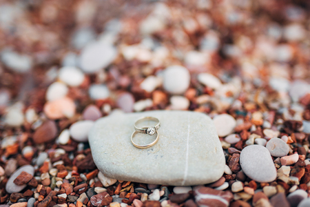 Wedding rings of newlyweds on beach pebbles. Engagement gold rings. Wedding in Montenegro. Фото со стока - 87578078