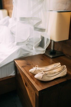 Cream shoes of the bride on green on a wooden table table. Wedding in Montenegro. Фото со стока