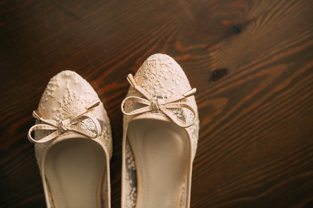 Cream shoes of the bride on green on a wooden table table. Wedding in Montenegro. Фото со стока - 87474364