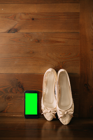 Cream bride shoes on a wooden background and phone with a green screen. Wedding in Montenegro.