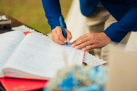 Newlyweds put their signatures in the act of registering a marriage at a wedding ceremony in Montenegro. Stock Photo