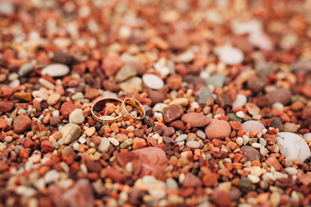 Wedding rings of newlyweds on beach pebbles. Engagement gold rings. Wedding in Montenegro. Stock Photo