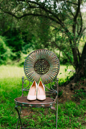 boudoir: Brides shoes on a metal chair vintage