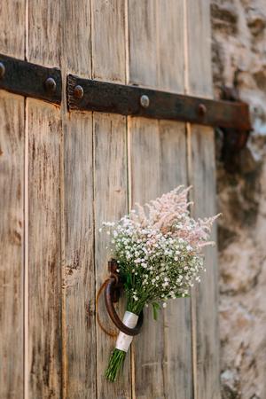 Wedding bridal bouquet of Gypsophila on an old wooden door. Wedding in Montenegro, Adriatic. 版權商用圖片