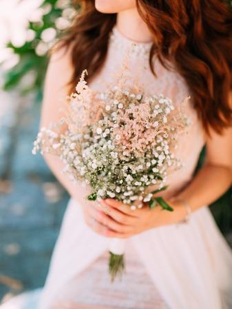 Wedding bridal bouquet of Gypsophila in the hands of the bride. Wedding in Montenegro.