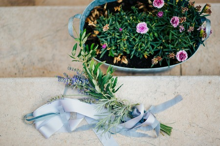 Wedding bouquet of lavender with ribbon on a stone background