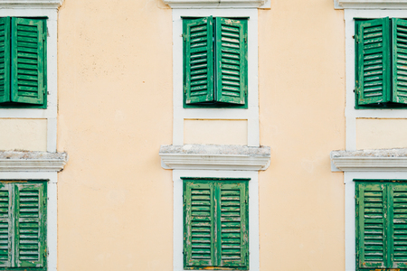 Green window shutters. The facade of houses in Montenegro.