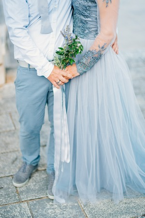 Lavender Wedding bouquet in hands of the bride in white-blue dress