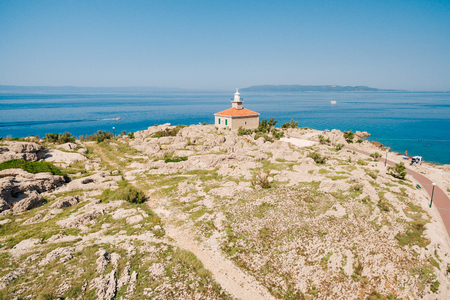 White stone lighthouse settled on the coast in Adriatic Sea. Clear daylight view of abandoned and renovated lighthouse Saint Peter, Makarska, Croatia. The coastal lighthouse which is no more in use.