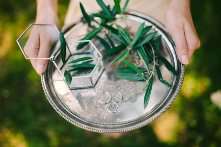 old photo: Wedding rings on a silver tray with olive branches in their hands of the bride. Wedding jewelry.