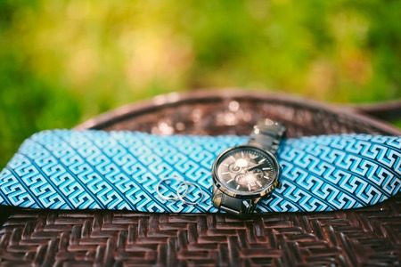 Watch the bride and rings lie on a blue tie. Photo Camping on a wooden background.