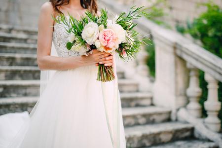 Ramalhete de peônias nas mãos da noiva. Casamento em Montenegro. Foto de archivo - 85749627