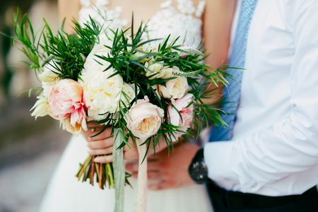 Wedding bouquet of peonies in the hands of the bride. Wedding in Montenegro.