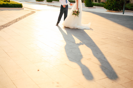 The shadow of the couple on the floor. Silhouette of the shadow of the newlyweds on the asphalt in Montenegro.