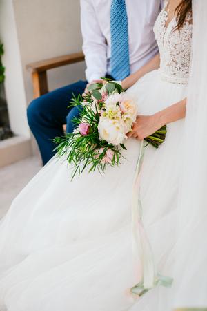 Wedding bouquet of peonies in the hands of the bride. Wedding in Montenegro.