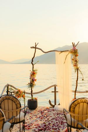 Wooden arch for the wedding ceremony at sunset. On the shore of the Bay of Kotor, Tivat, Montenegro Фото со стока