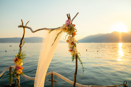 Arco de madera para la ceremonia de boda al atardecer. En la costa de la Bahía de Kotor, Tivat, Montenegro Foto de archivo - 86858412