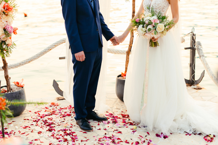 The newlyweds hold hands at the wedding ceremony. Couple holding hands. Wedding in Montenegro.