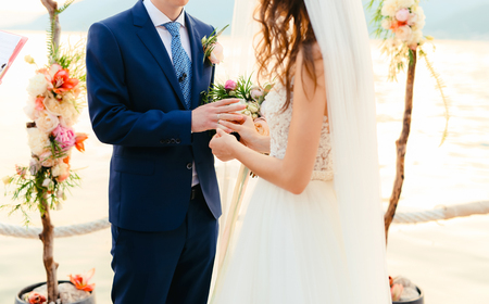 fingers put together: The bride puts the ring on the bridegroom at the wedding ceremony. Wedding in Montenegro.