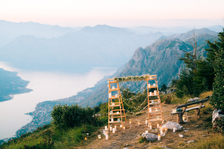 Wedding in Montenegro. Wedding Arch on Mount Lovcen, Montenegro. Kotor Bay View. Wooden arch with candles