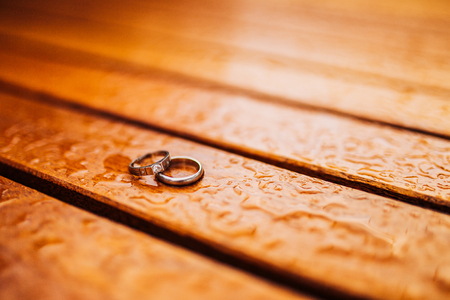 Gold wedding rings on a wooden background Stock Photo