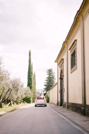 Beautiful bride standing up in a convertible with her back turned to the camera in front of the Medici Villa of Lilliano Wine Estate, Tuscany, Italy.