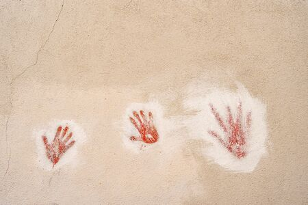 Red handprints on the wall. Two childrens handprints and one adult handprint on a stone wall