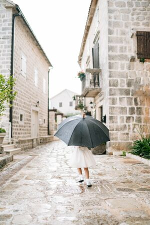 The child poses with an umbrella. A little girl in dress stands outside under an umbrella black during the rain.