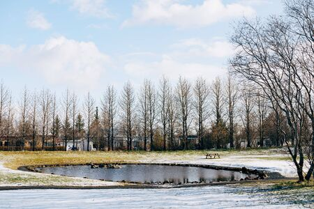 A lake with a table with benches, in a snow-covered park in Reykjavik, Iceland