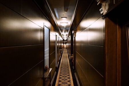 Dark hotel corridor. A long carpet with a pattern, wooden wall cladding. Deserted hotel corridor Banque d'images