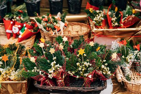 Showcase of bunch of holly the Christmas market. Envelopes with christmas tree branch, bump, berries, stars. New Years souvenirs. Holly branches with red berries in baskets 写真素材