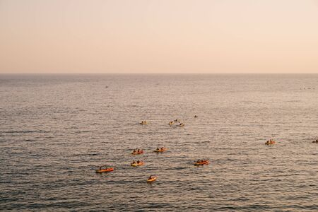 A group of tourists travel in pairs kayaks by sea against the sunset sky, near old town of Dubrovnik, Croatia. Concept banner travel. Aerial top view.