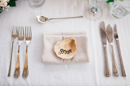 Close-up of a wedding dinner table. The inscription GROOM on the shell in center of the table. Serving a table - knives, forks, glasses, wine glasses, against background of gray tablecloth