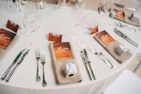 Close-up of a wedding dinner table. Brown napkins with an enclosed menu, forks and knives, wine glasses against the backdrop of a cream tablecloth with a dining path. Small gift boxes from newlyweds