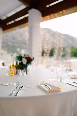 Close-up of a wedding dinner table - forks lie on a napkin. Table in the background of the garland, on the table are glasses for wine and glasses, floral composition and carafe with olive oil