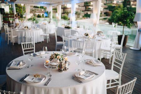Empfang am Hochzeitstisch. Runder Banketttisch mit weißer Tischdecke und weißen Chiavari-Stühlen. Hochzeit unter dem Zelt.