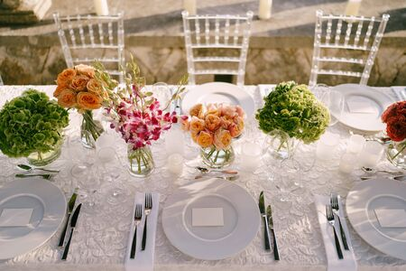 Wedding dinner table reception. View from above on white round plates close-up. Bouquets of pink, orange, green flowers. Pink roses, small orange roses. Top view
