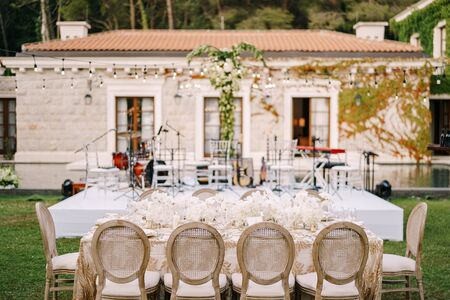 Elegant tables for guests with cream tablecloths with patterns, on green lawn, with garlands and chandeliers hanging over them. Chairs with a round back. An open-air wedding.